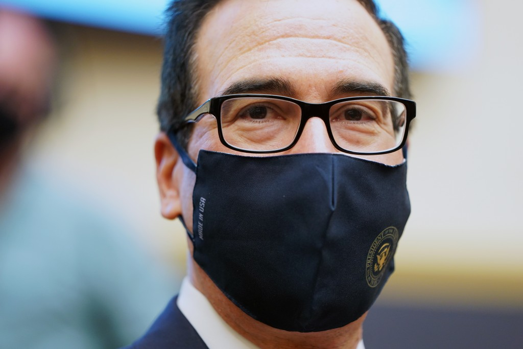 Treasury Secretary Steven Mnuchin wears a face mask as he arrives for a House Financial Services Committee hearing about the government's emergency ai...