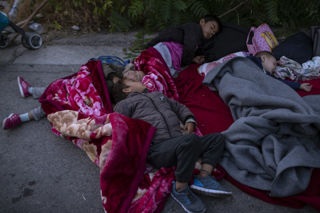希臘勒斯博島(Lesbos)難民營失火後,失去住居的小孩在附近道路旁席地而睡。(美聯社圖片)