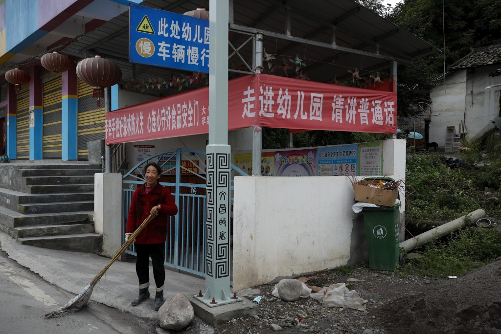 "A woman sweeps outside a kindergarten school displaying a banner which reads: ""Please speak Mandarin when you enter the school"" at a village in Ganluo..."