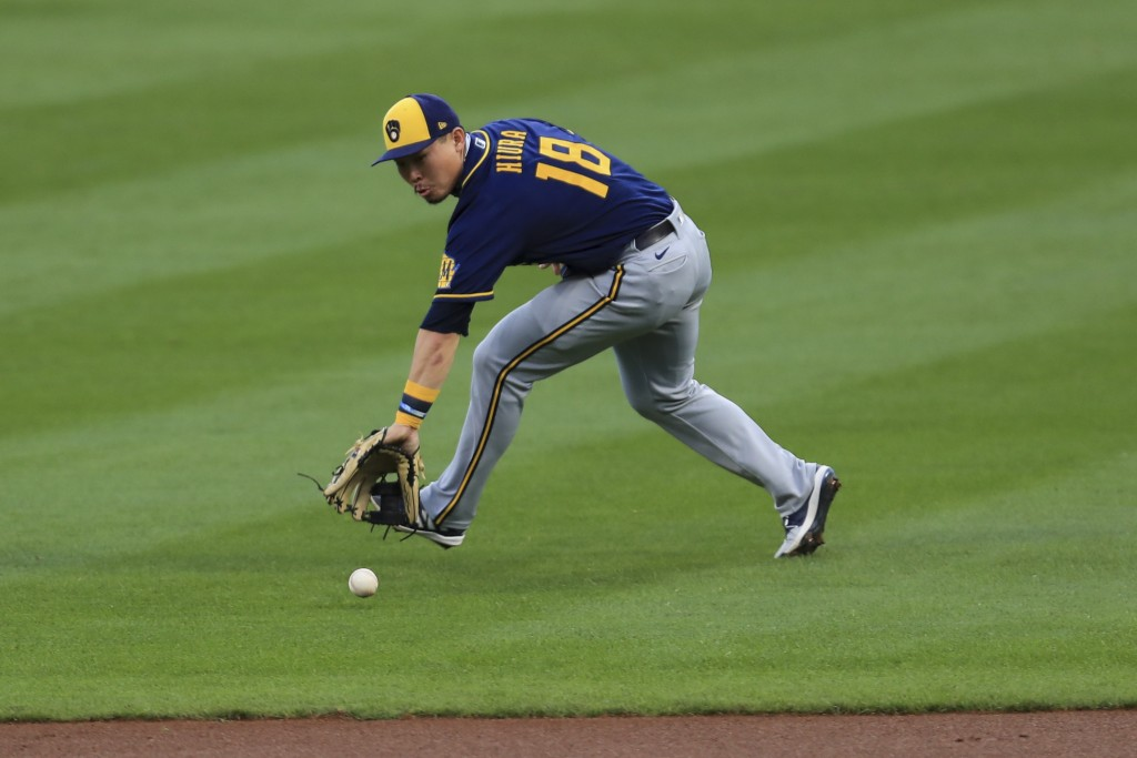 Milwaukee Brewers' Keston Hiura fields the ball and throws out Cincinnati Reds' Joey Votto at first base in the first inning during a baseball game in...