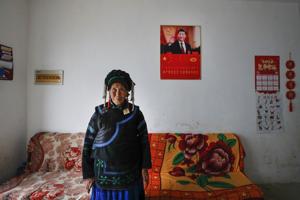A minority Yi woman stands inside her house displaying a poster of Chinese President Xi Jinping, in Xujiashan village in Ganluo County, southwest Chin...