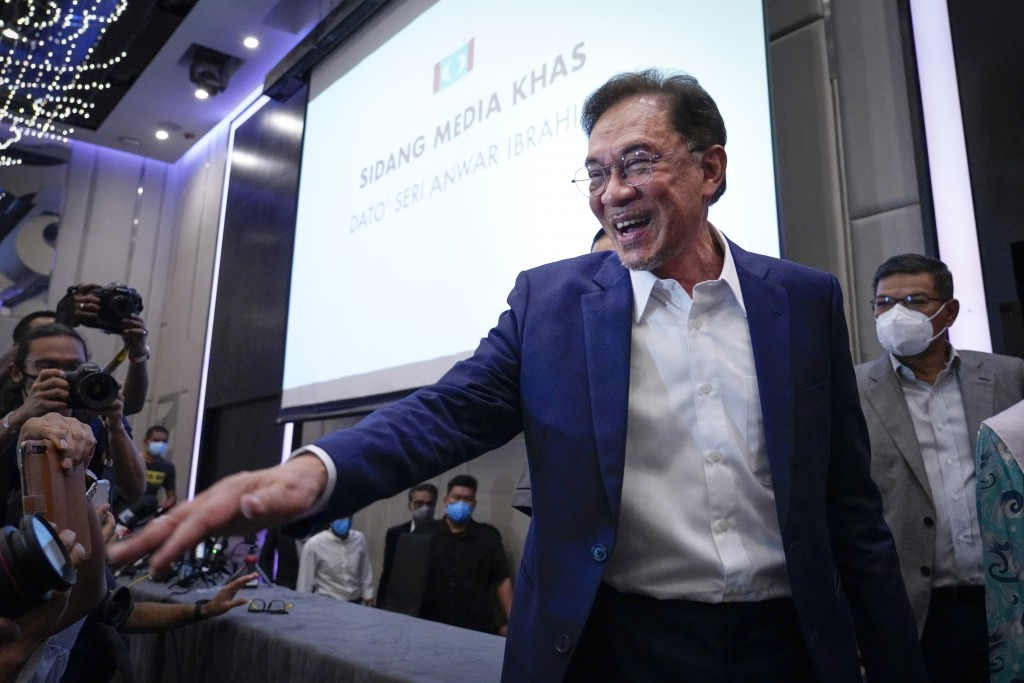 Malaysia's opposition leader Anwar Ibrahim gestures as he leaves after a press conference in Kuala Lumpur, Wednesday, Sept. 23, 2020. Anwar said he ha...