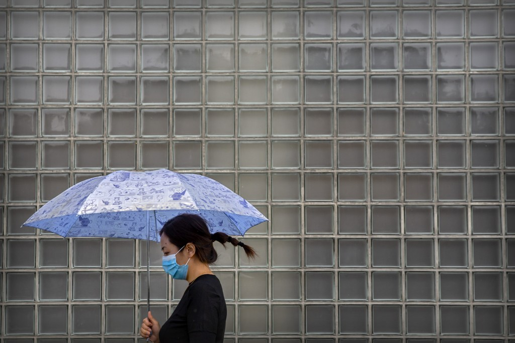 A woman wearing a face mask to protect against the coronavirus walks past a shopping mall on a rainy day in Beijing, Wednesday, Sept. 23, 2020. Even a...