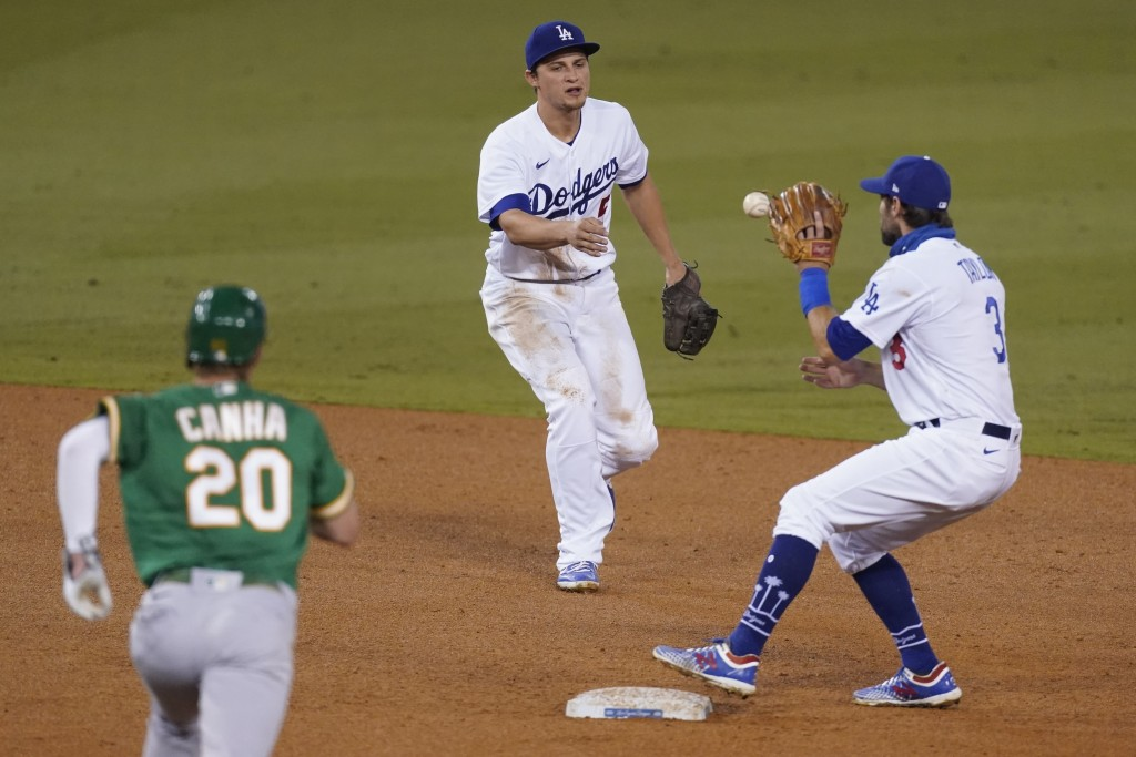 Los Angeles Dodgers shortstop Corey Seager, center, tosses the ball to second baseman Chris Taylor to put out Oakland Athletics' Mark Canha on a groun...