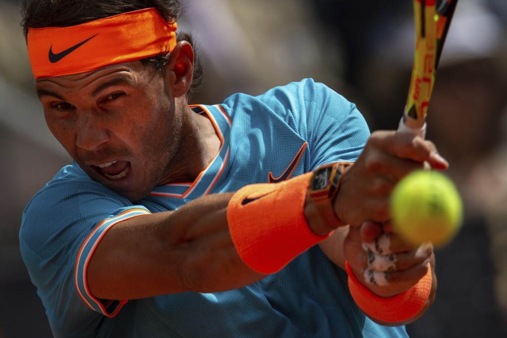 FILE - In this May 8, 2019, file photo, Rafael Nadal, from Spain, returns the ball to Felix Auger-Aliassime, from Canada, during the Madrid Open tenni...