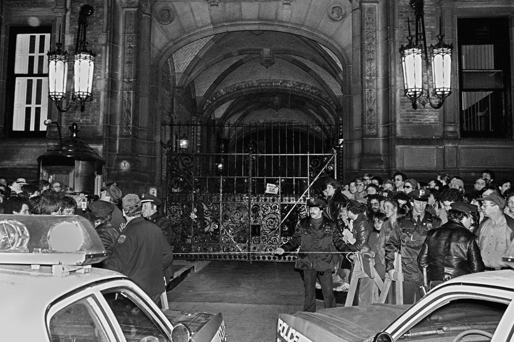 FILE - In this Dec. 9, 1980, file photo, a crowd gathers outside the Dakota apartment building after John Lennon, who lived there, was shot hours earl...