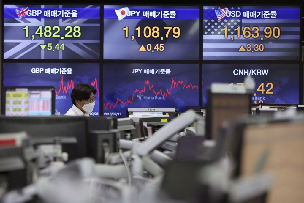 A currency trader watches monitors at the foreign exchange dealing room of the KEB Hana Bank headquarters in Seoul, South Korea, Wednesday, Sept. 23, ...