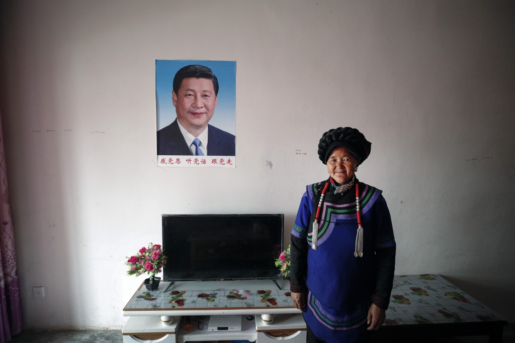 A minority Yi woman stands inside her apartment house displaying a portrait of Chinese President Xi Jinping, in Yuexi County, southwest China's Sichua...
