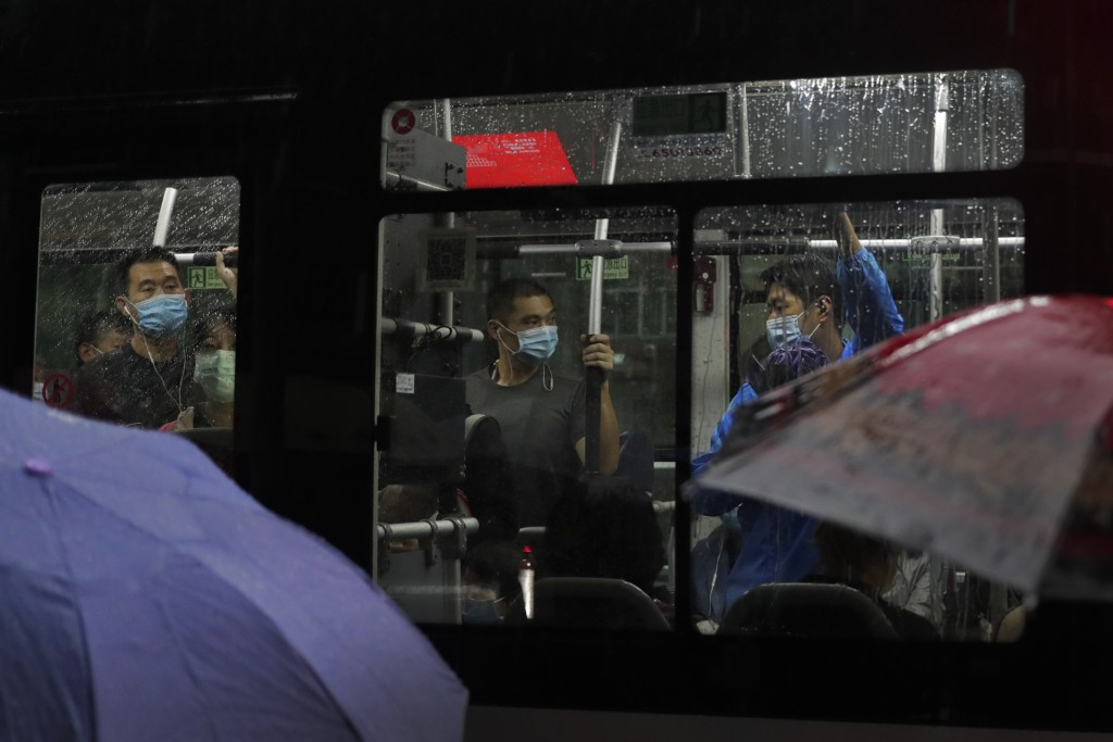 Commuters wearing face masks to help curb the spread of the coronavirus ride on a bus in the rain in Beijing, Wednesday, Sept. 23, 2020. Xi Jinping, C...