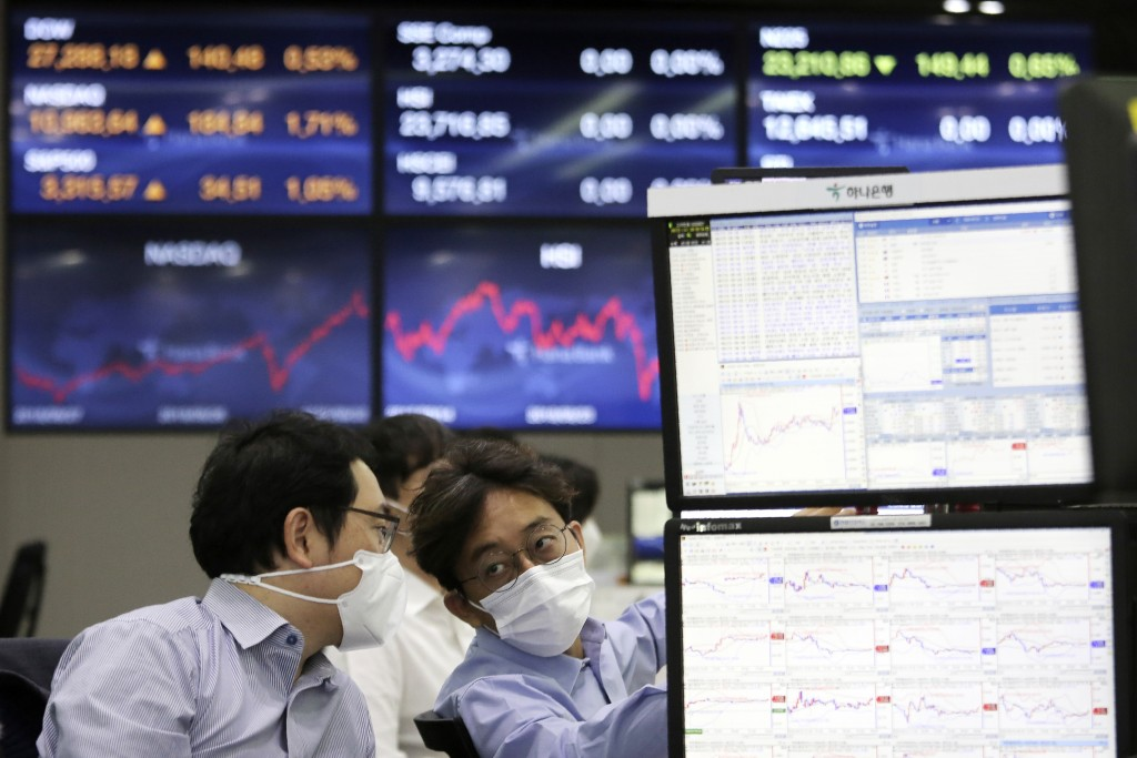 Currency traders work at the foreign exchange dealing room of the KEB Hana Bank headquarters in Seoul, South Korea, Wednesday, Sept. 23, 2020. Asian m...