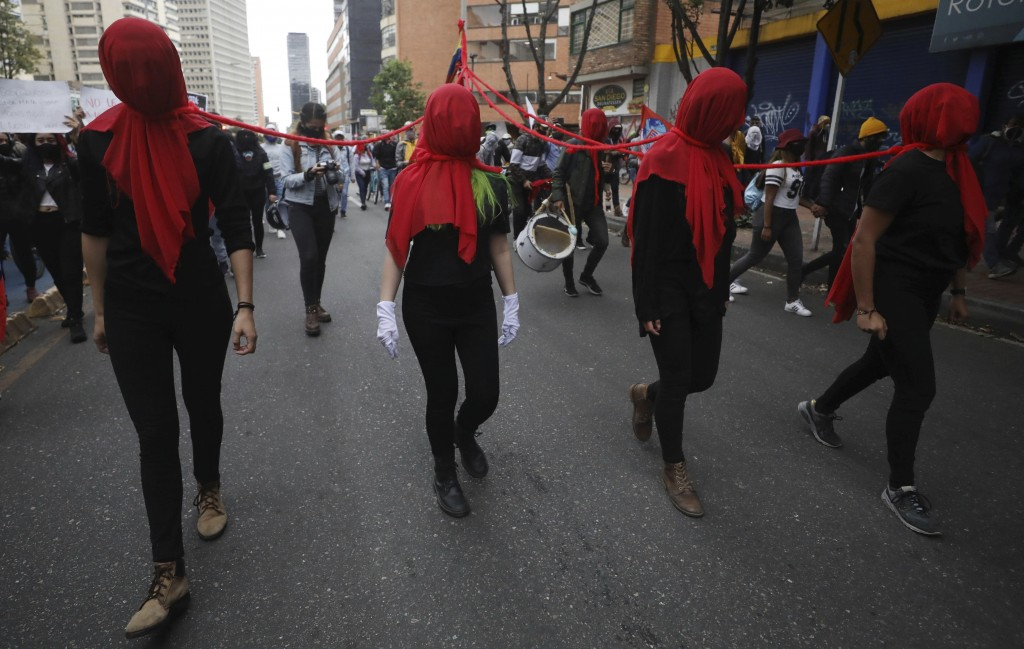 Women wearing red shrouds march during a demonstration against a wave of massacres, in Bogota, Colombia, Monday, Sept. 21, 2020. Rather than a nationa...