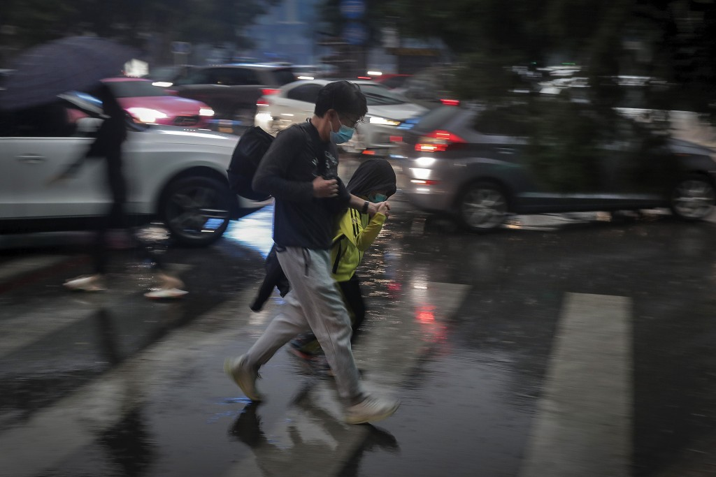 A man and a child wearing face masks to help curb the spread of the coronavirus walk across a street in the rain as motorists are clogged with heavy t...