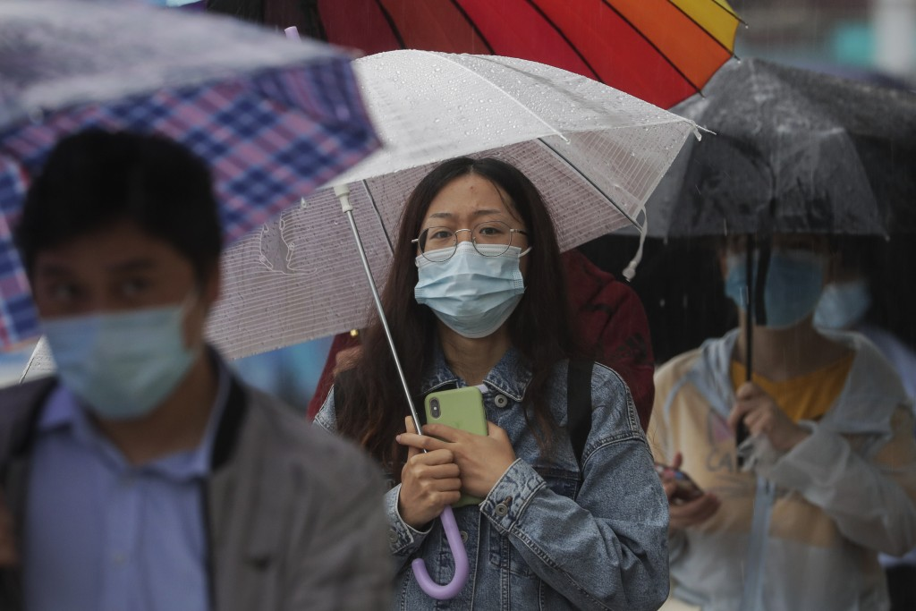 People wearing face masks to help curb the spread of the coronavirus walk in the rain on a street in Beijing, Wednesday, Sept. 23, 2020. Xi Jinping, C...