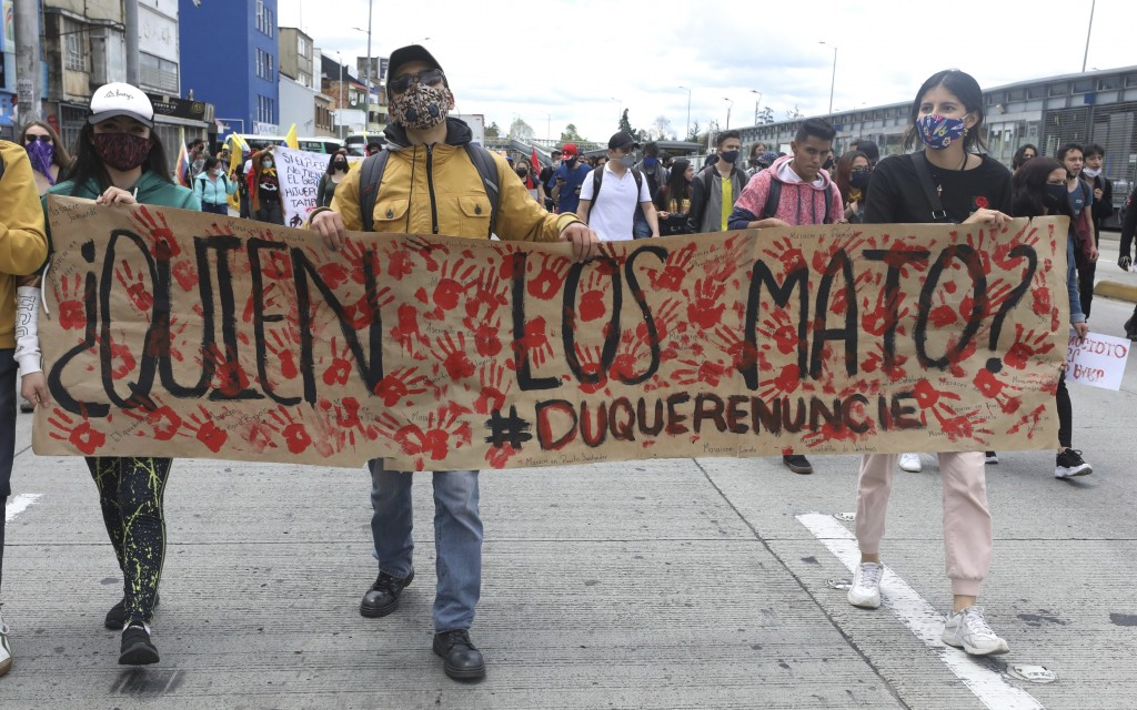 "University students march holding a poster with a message that reads in Spanish: ""Who killed them?"" during a demonstration against a wave of massacres..."