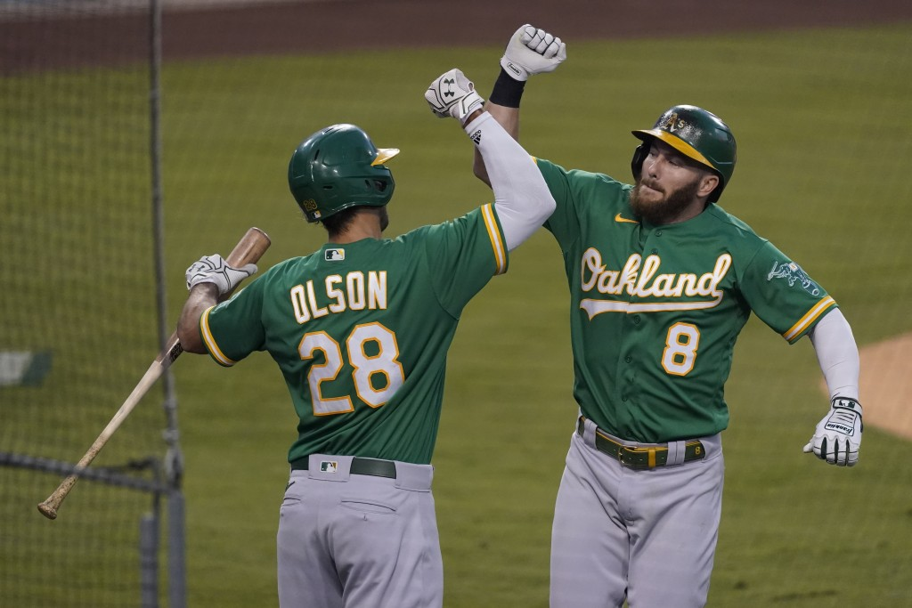 Oakland Athletics' Robbie Grossman, right, celebrates his solo home run with Matt Olson during the first inning of a baseball game against the Los Ang...