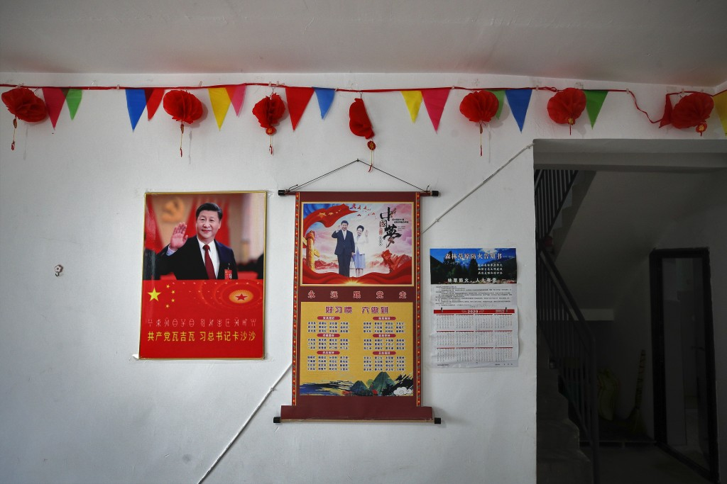Posters showing images of Chinese President Xi Jinping and his wife Peng Liyuan are displayed on a wall of a home of members of the Yi minority group ...
