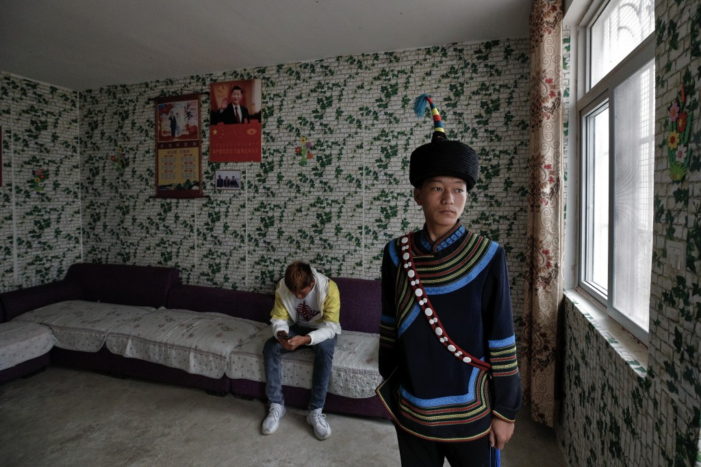 A Yi ethnic minority member stands inside his house displaying posters of Chinese President Xi Jinping and his wife Peng Liyuan, in Xujiashan village ...
