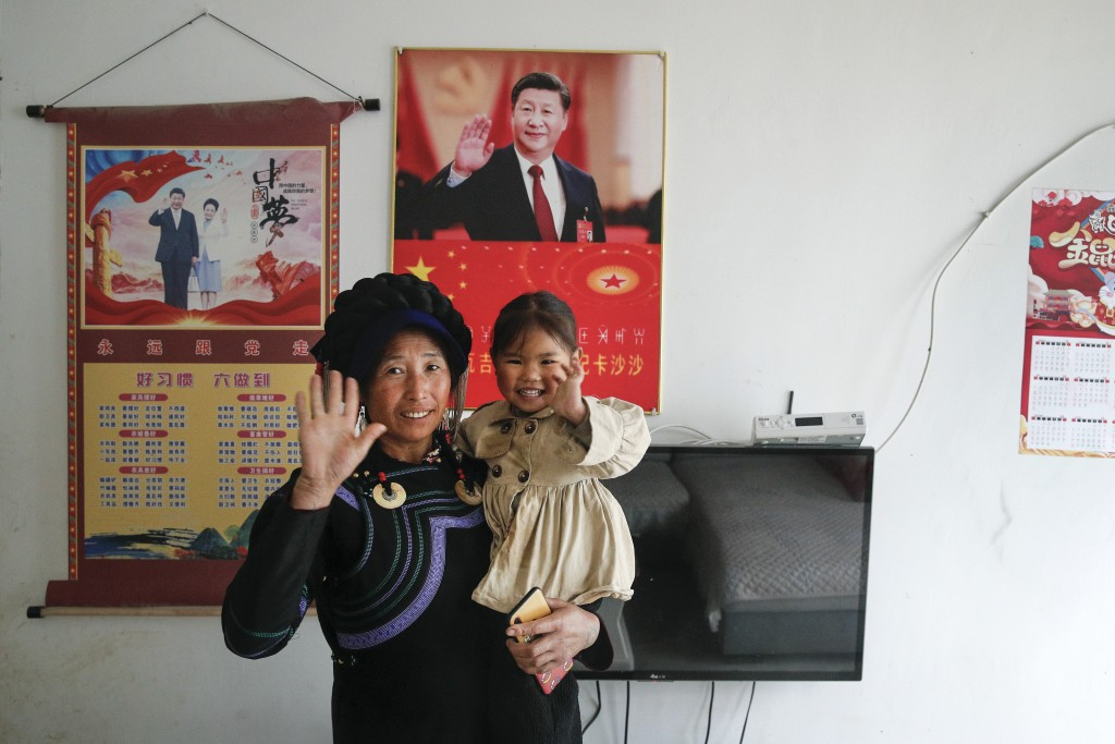 A minority woman and a child wave near posters showing images of Chinese President Xi Jinping and his wife Peng Liyuan on display on a wall at her hou...