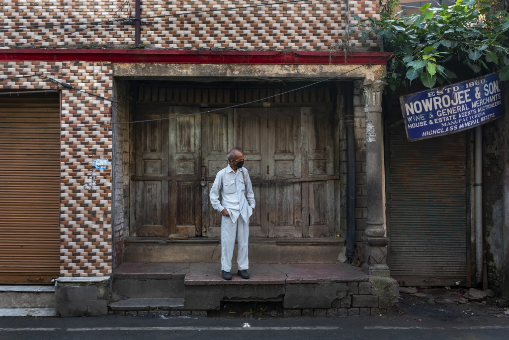 A man wearing a mask as protection against the coronavirus stands in front of a closed shop in Dharmsala, India, Wednesday, Sept. 23, 2020. The nation...