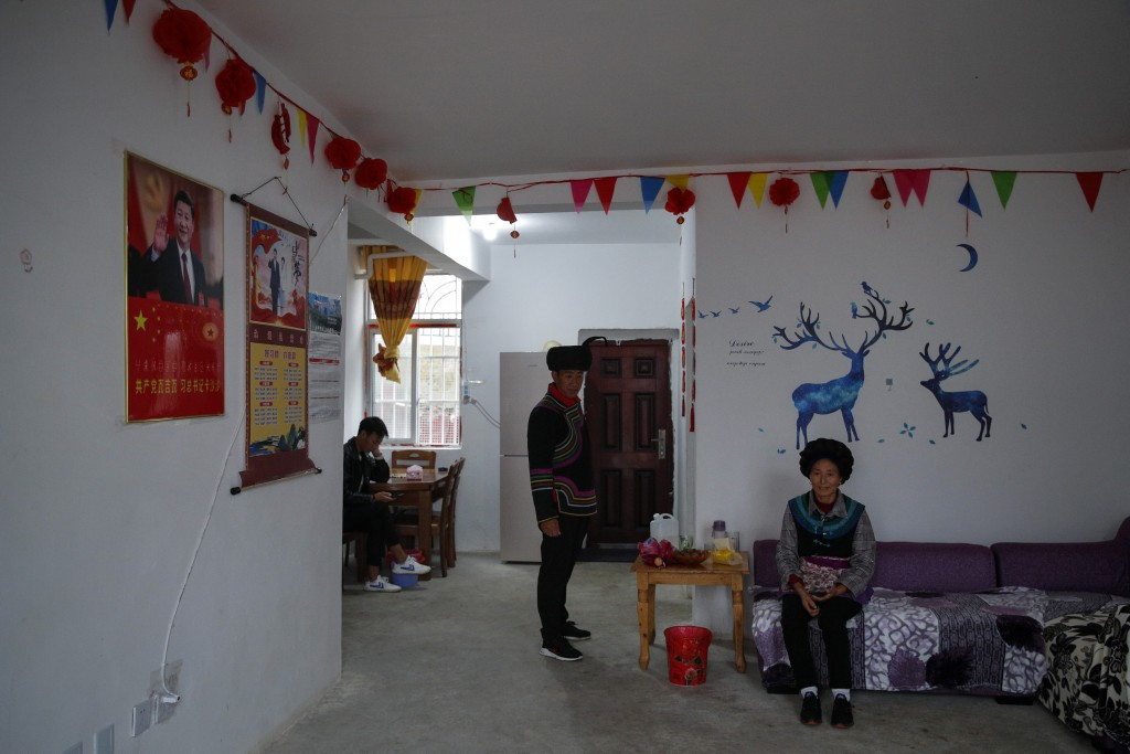An ethnic minority Yi family rests near posters of Chinese President Xi Jinping in their village house built by the Chinese government in Ganluo count...