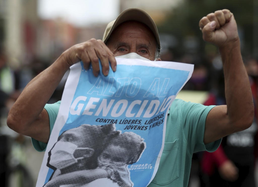 "A protester holds a poster with a message that reads in Spanish: ""Stop the Genocide,"" during a demonstration against a wave of massacres, in Bogota, C..."