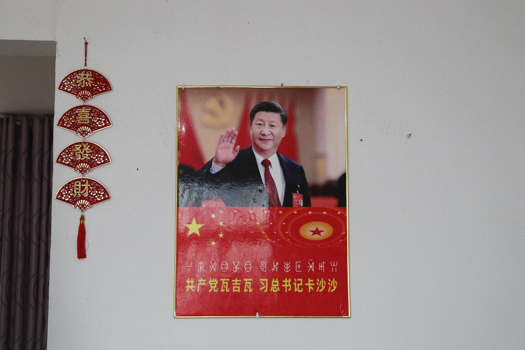 A poster showing an image of Chinese President Xi Jinping is displayed on a wall at a home of members of the Yi minority group in Xujiashan village in...