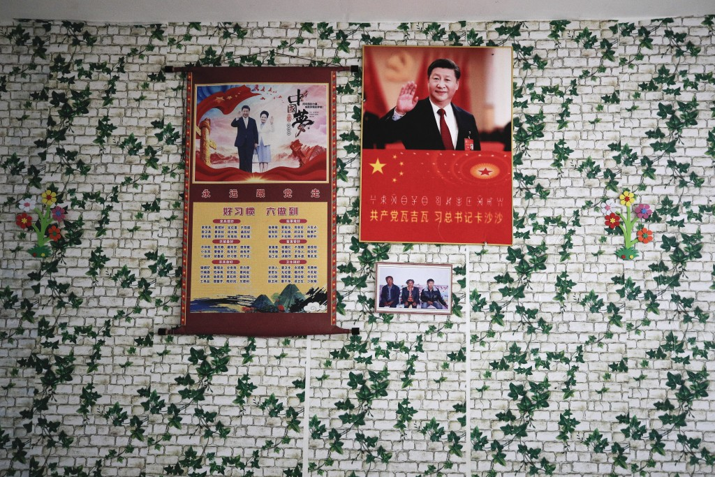 Posters of Chinese President Xi Jinping and his wife Peng Liyuan are displayed on a wall with a photo of members of the Yi minority group inside their...
