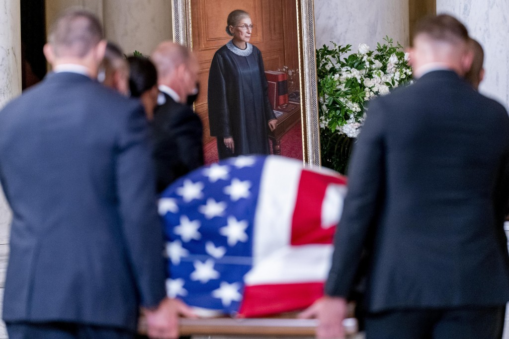 The flag-draped casket of Justice Ruth Bader Ginsburg, carried by Supreme Court police officers, arrives in the Great Hall at the Supreme Court in Was...