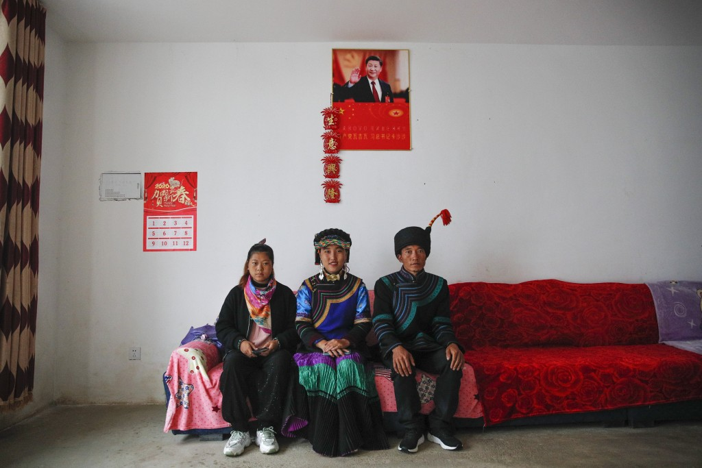 A minority Yi family sits inside their home displaying a poster of Chinese President Xi Jinping in Xujiashan village in Ganluo County, southwest China...