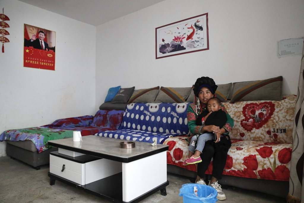 A minority Yi woman and her child sit inside her house displaying a poster of Chinese President Xi Jinping, left, in Xujiashan village in Ganluo Count...