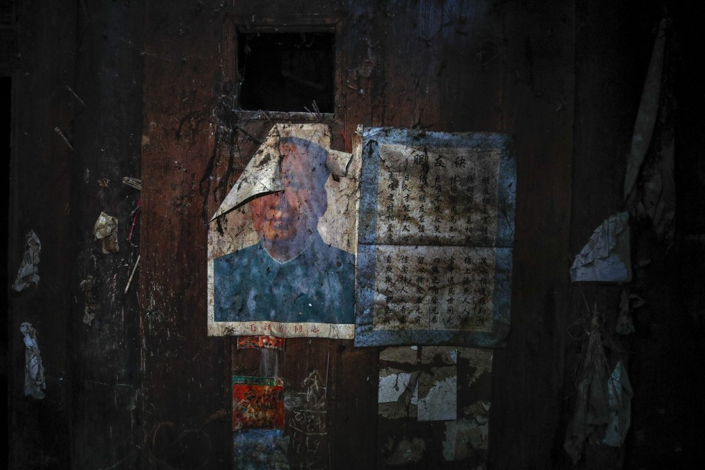 A partially damaged portrait of former leader Mao Zedong is seen inside an abandoned old house belonging to a member of Yi ethnic minority, in Qingshu...