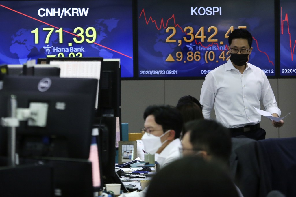 A currency trader walks with documents at the foreign exchange dealing room of the KEB Hana Bank headquarters in Seoul, South Korea, Wednesday, Sept. ...