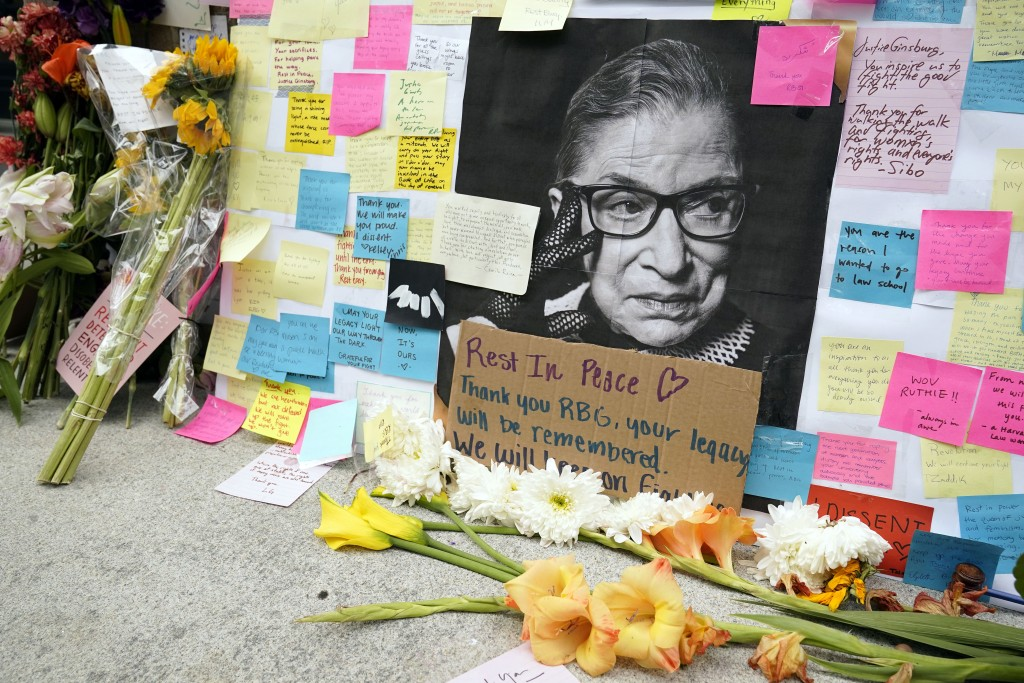 A memorial to U.S. Supreme Court Justice Ruth Bader Ginsburg includes a photograph of the late Justice, Tuesday, Sept. 22, 2020, outside the Harvard L...