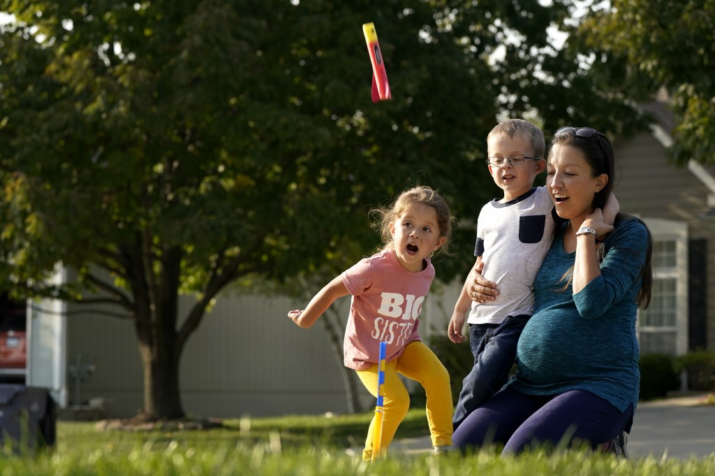 Claire Reagan plays with her kids Evan, 5, and Abbie, 3, Monday, Sept. 21, 2020, outside her home in Olathe, Kan. Reagan is keeping her son from start...