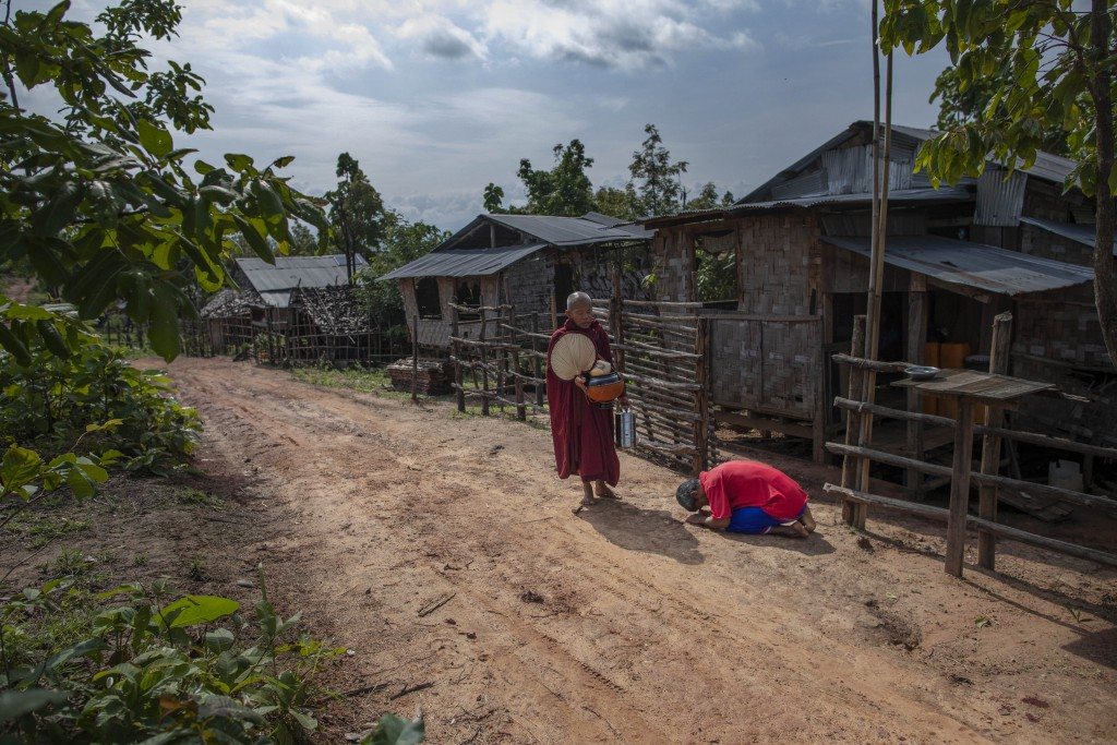 Zin Ko Ko Htwe, who was trafficked twice, bows after offering alms to a Buddhist monk outside his mother's house in Myawaddy, Myanmar, Friday, June 14...