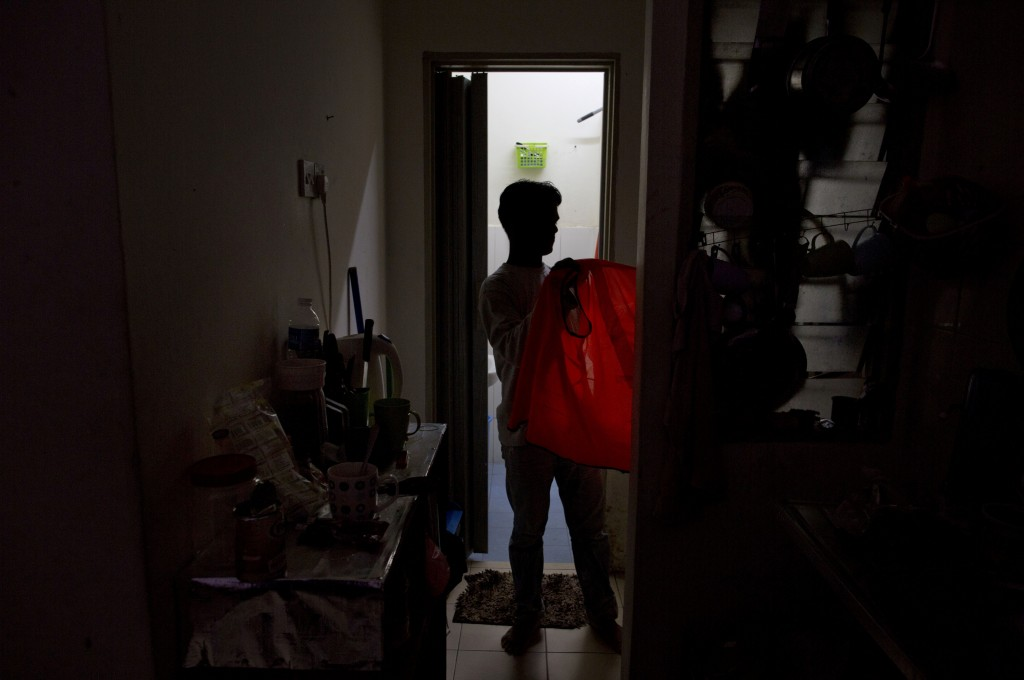 Shamshu, a member of Myanmar's long-persecuted Rohingya minority, changes clothes upon returning home in peninsular Malaysia, Monday, March 4, 2019. S...