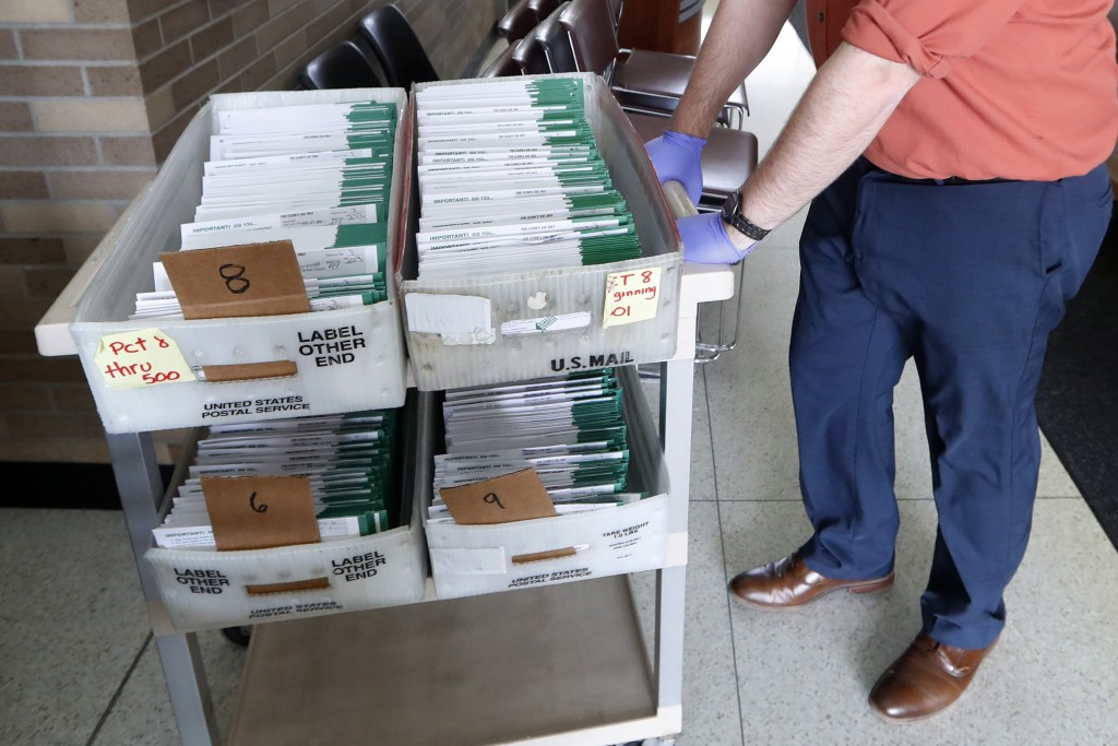FILE - In this May 5, 2020, file photo, absentee ballots to be counted are moved at City Hall in Garden City, Mich. Data obtained by The Associated Pr...