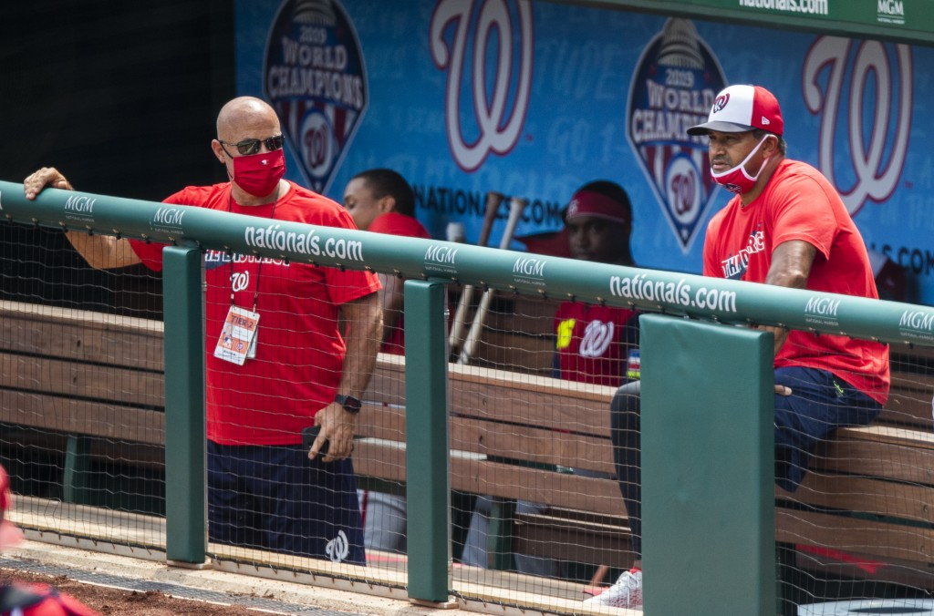 FILE  - In this Sunday, Aug. 2, 2020, file photo, Washington Nationals manager Dave Martinez, right, with General Manager Mike Rizzo, left, watch from...