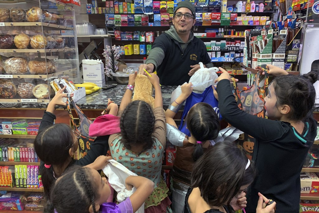 FILE - In this Oct. 31, 2018 file photo, a local convenient store worker, hands out candy to trick or treaters on Halloween in Brooklyn Borough of New...