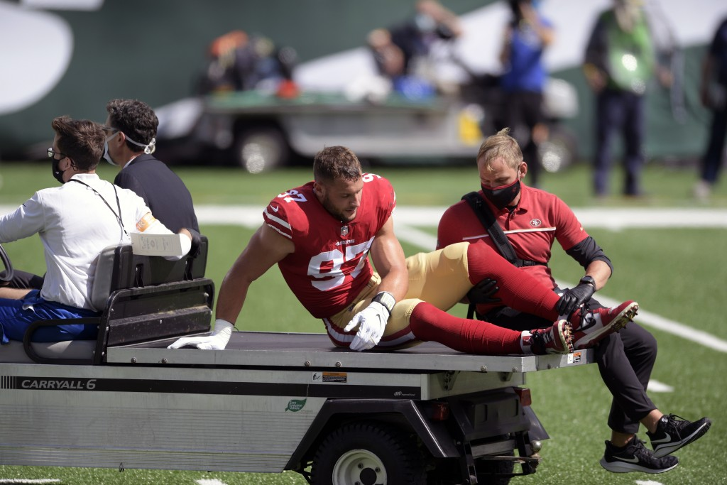 San Francisco 49ers defensive end Nick Bosa (97) is driven off the field after being injured during the first half of an NFL football game against the...