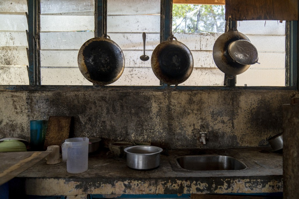 Pots and pans hang in the kitchen of workers' living quarters in a palm oil plantation run by the government-owned Felda in Malaysia in early 2020. Ju...
