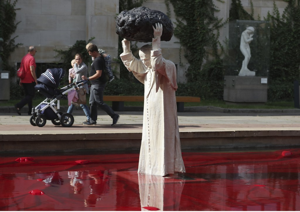 """Visitors to the National Museum walk past a new statue of the late pope, St. John Paul II, throwing a stone at a """"Poisoned Well""""  just hours before it..."""