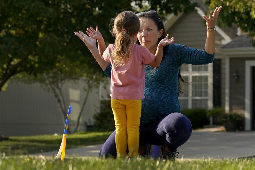 Claire Reagan plays with her daughter Abbie, 3, Monday, Sept. 21, 2020, outside her home in Olathe, Kan. Reagan is keeping her son Evan, 5, from start...
