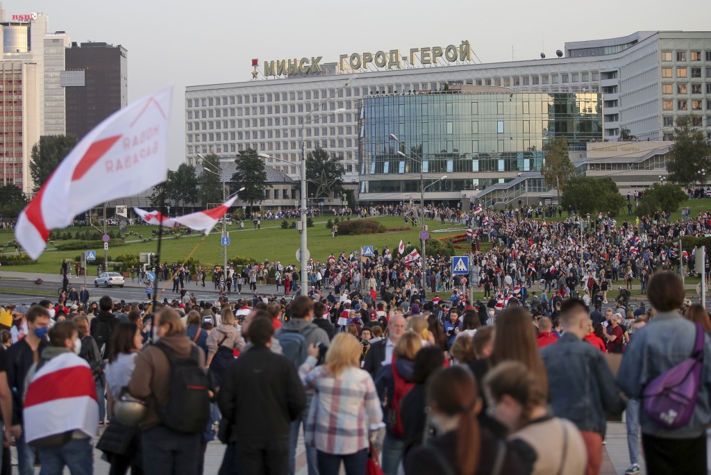 People with old Belarusian national flags gather during an opposition rally to protest the presidential inauguration in Minsk, Belarus, Wednesday, Sep...