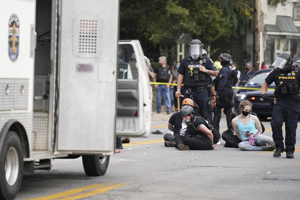 Louisville police detain a a group who marched, Wednesday, Sept. 23, 2020, in Louisville, Ky. A grand jury has indicted one officer on criminal charge...