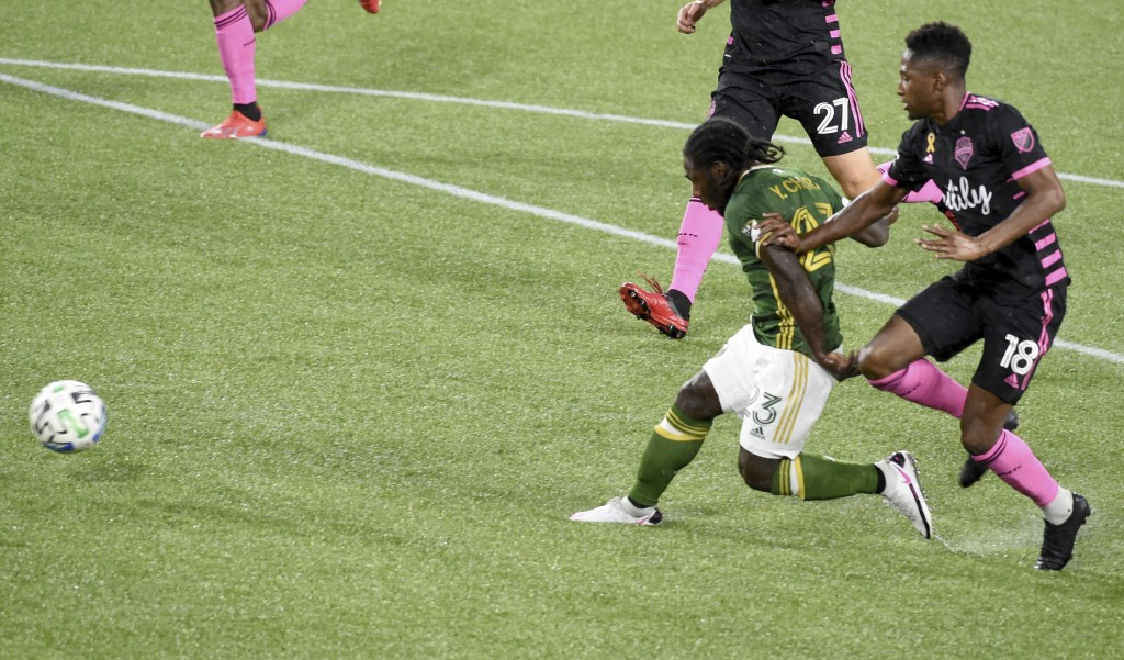 Portland Timbers forward Yimmi Chara (23) scores a goal as Seattle Sounders' Yeimar Gomez, right, defends during the first half of an MLS soccer match...