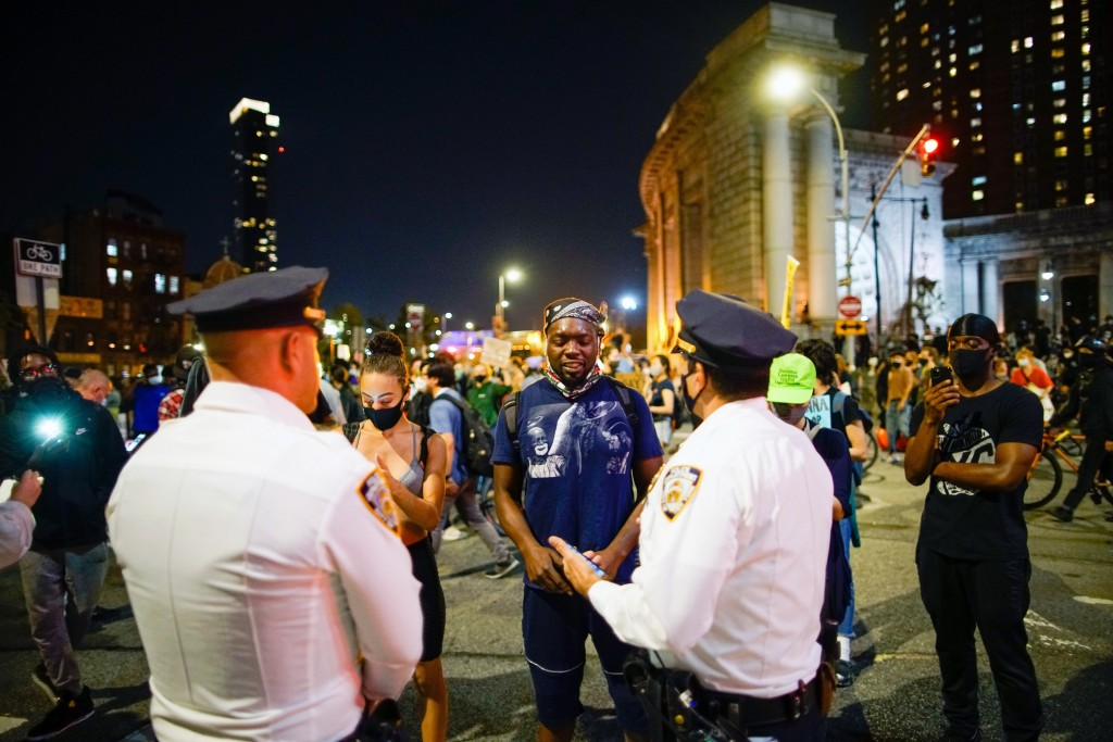 People approach NYPD officers as they take part in a protest following a Kentucky grand jury's decision not to indict any police officers for the kill...