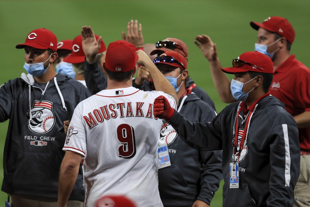 Cincinnati Reds' Mike Moustakas fist bumps members of the Reds' grounds crew after a baseball game against the Milwaukee Brewers in Cincinnati, Wednes...