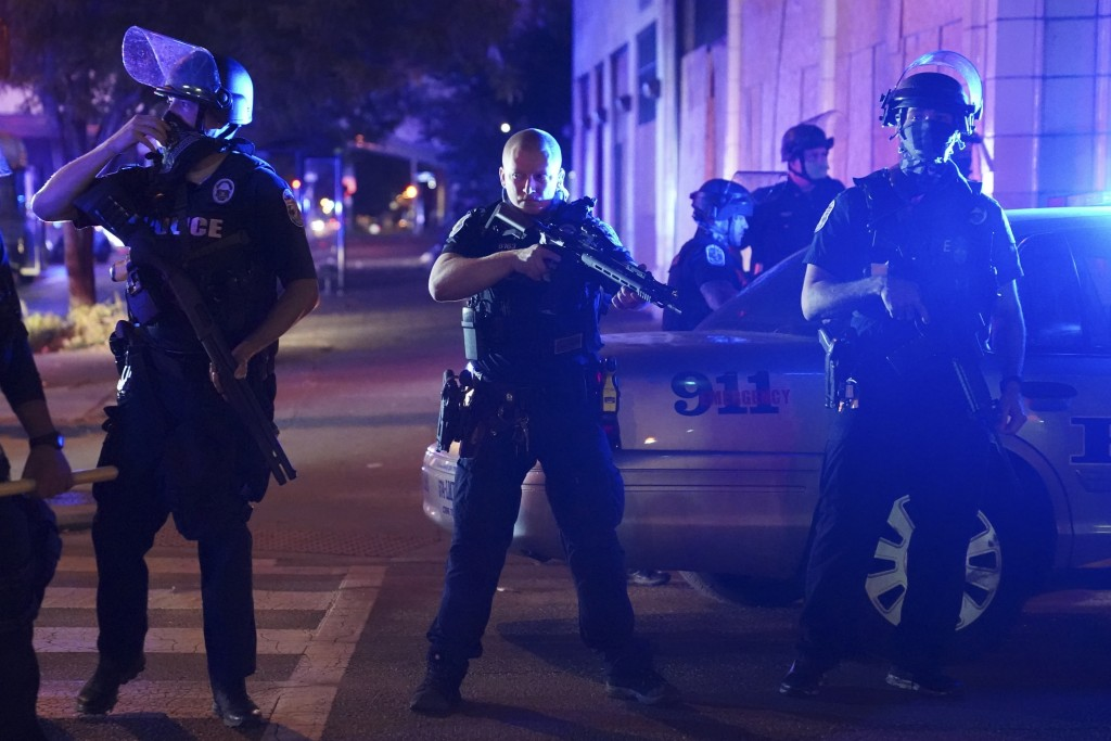 Police stand at an intersection after an officer was shot, Wednesday, Sept. 23, 2020, in Louisville, Ky. A grand jury has indicted one officer on crim...
