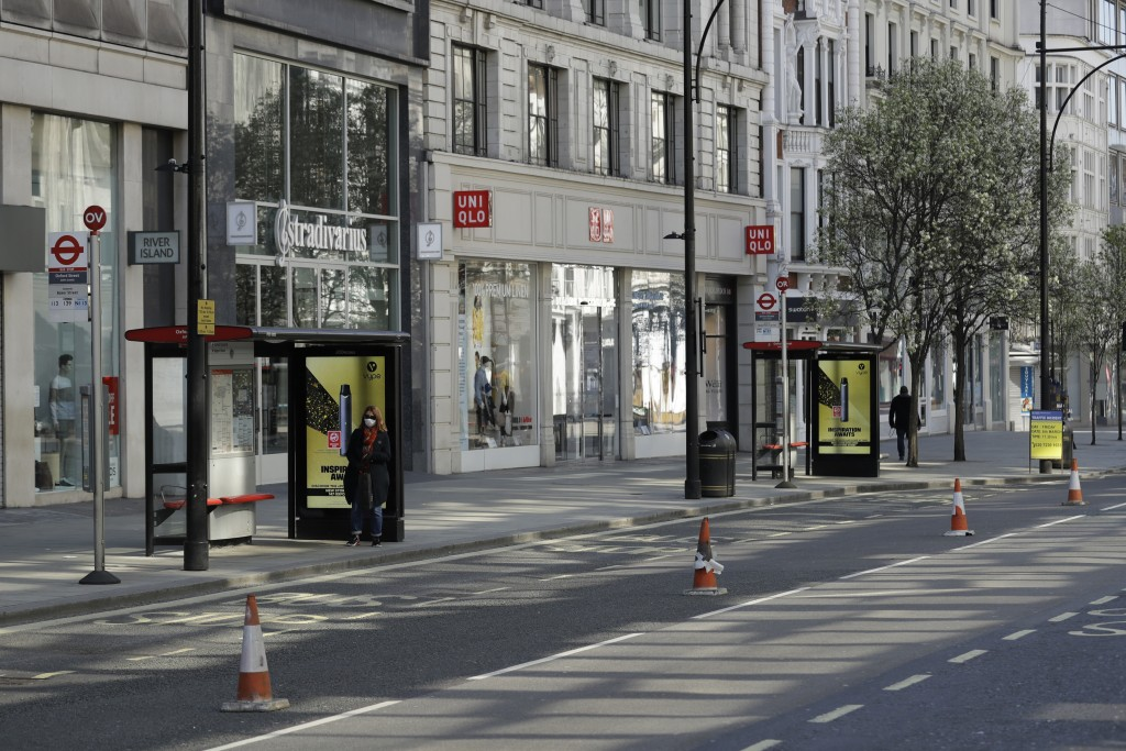FILE - In this Tuesday, March 24, 2020 file photo, a masked woman waits at a bus stop on a deserted Oxford Street in London. Britain botched its respo...